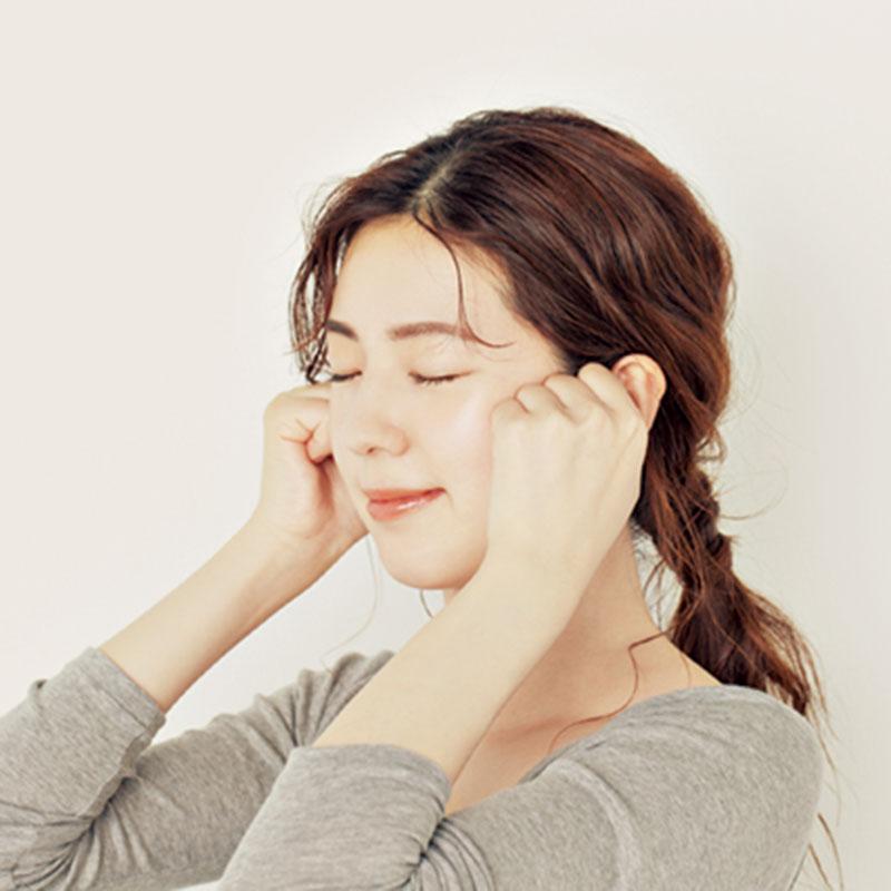 5.頬全体がほぐれてきたら、手をこぶしにしたまま、耳の前まですべらせます。これでぐっとすっきりとした顔立ちに近づきます。