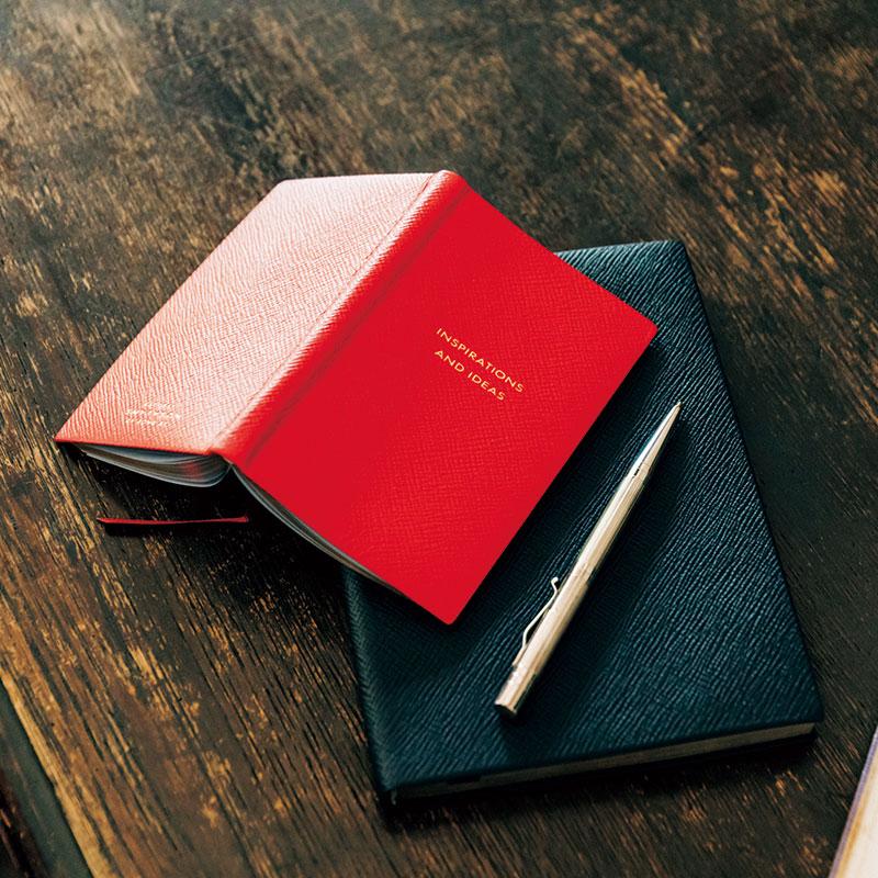 仕事で使う筆記用具もこだわりの品を使って。会議中のメモを取る何げないシーンでも、「あの人素敵」が叶いそう。ボールペン¥65,000ノート[赤]¥9,400[紺]¥25,000(すべてスマイソン/ヴァルカ ナイズ・ロンドン)