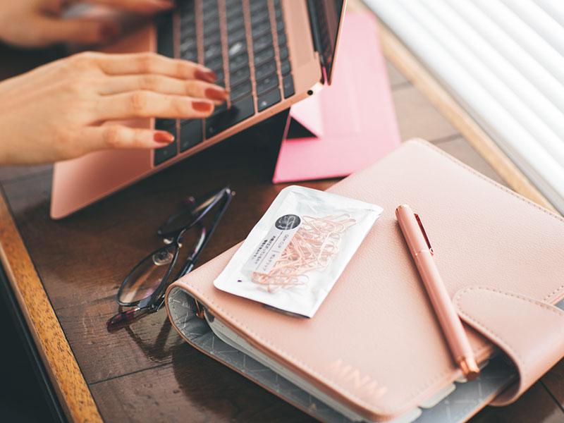 「起業して文具の輸入をしていた経験もあるほど文具が大好き。PCスタンド、手帳、ペン、クリップ、付箋まで、PCの色に合わせてピンクでコーディネート。仕事道具にこだわることで、丁寧な気持ちで仕事ができます」