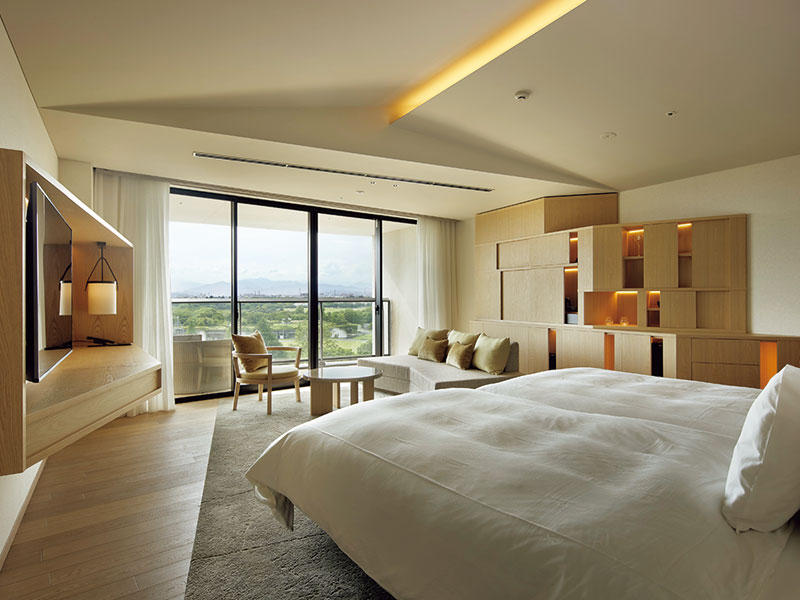 バルコニー越しに、昭和記念公園の緑が広がる。眺めを楽しめるようベッドは部屋中央に配置。