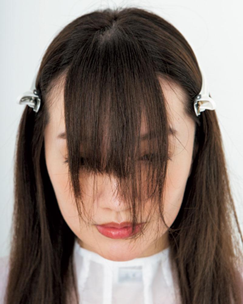 2.センターパートの分け目を頂点に、前髪が目尻に下りる幅で、高さ3㎝の三角形に分けます。