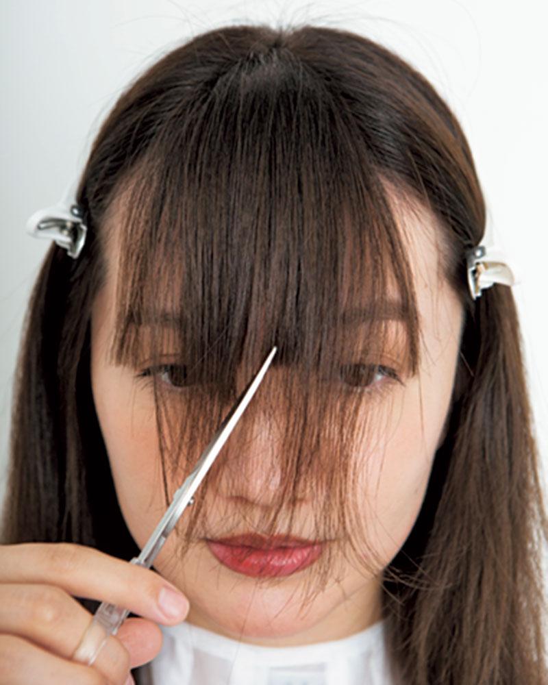 4.分けておいた上の髪も同じように、ハサミを縦に使って中心から目上の長さに切ります。