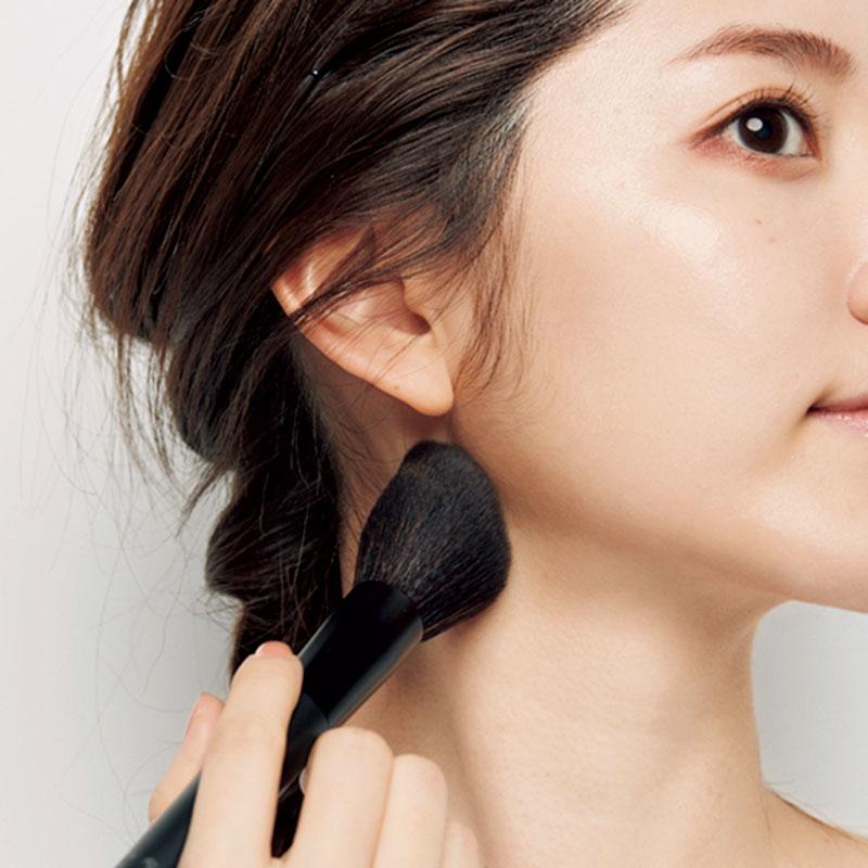 13. Jを大きめのブラシにとり、余分な粉を落としたら、耳下から顎先、顎の裏にも。首の側面にものせることで細い首を演出。