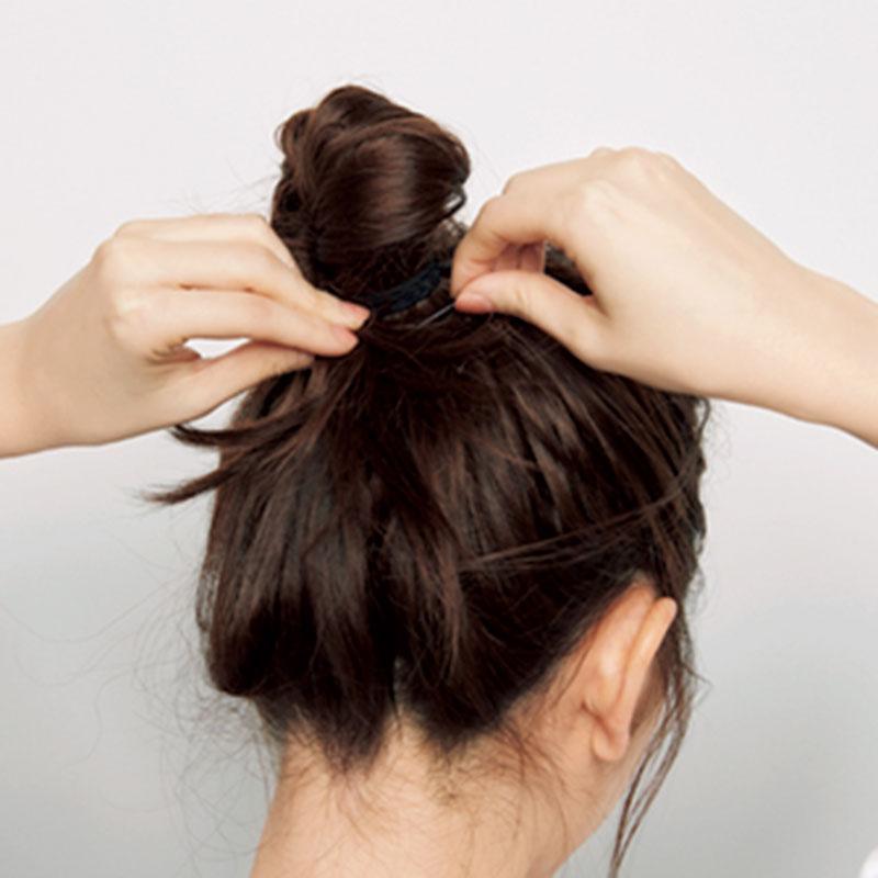 3.先ほどつくったポニーテールの毛をツイストして、ゴムに巻き付けます。毛先をピンで留めて、お団子にしましょう。