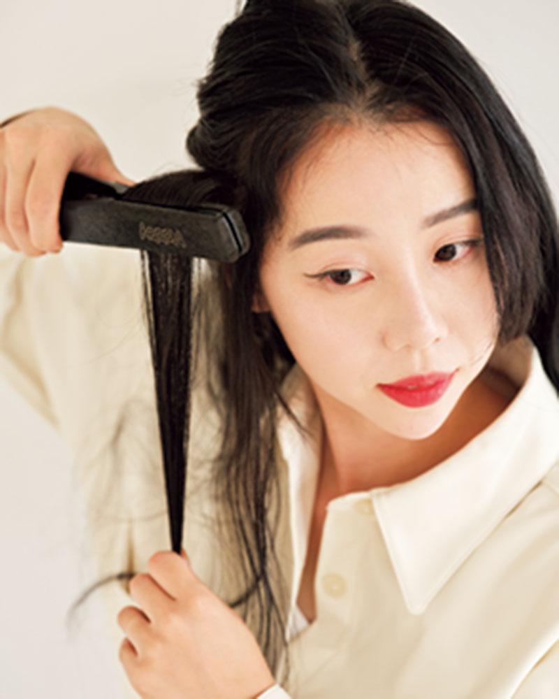 1.ストレートアイロンで髪の根元をはさんで立ち上げ、結んだときに表面が凸凹するように。