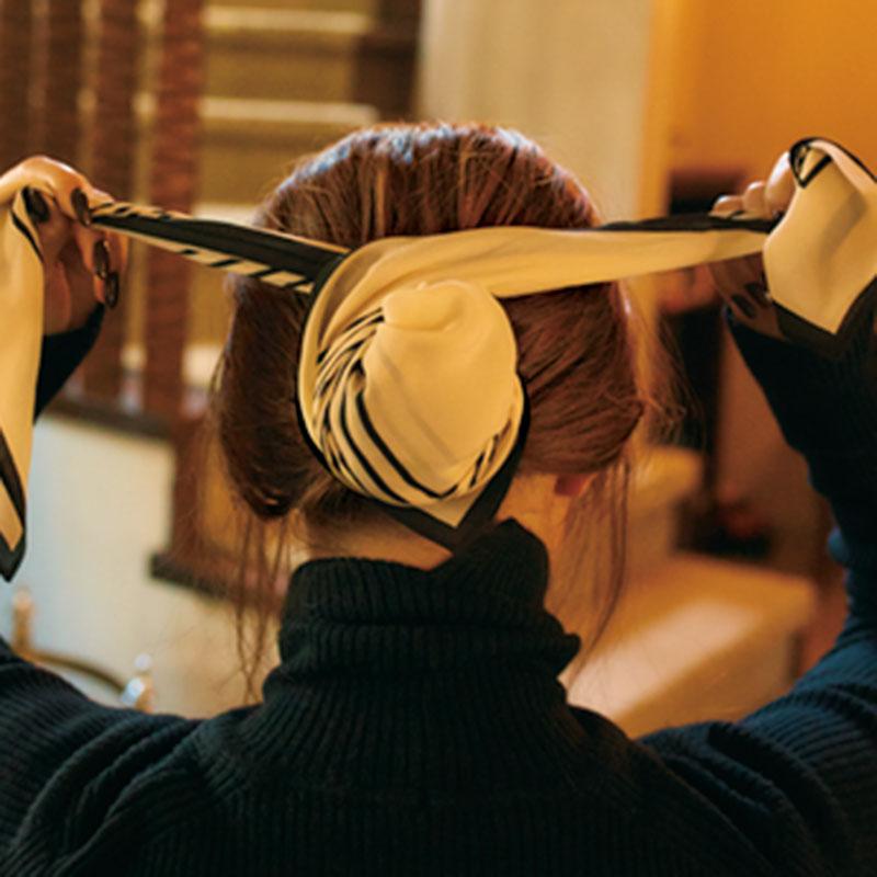⑤スカーフのサイドをねじったら、ゴムの上部分でスカーフを交差させます。