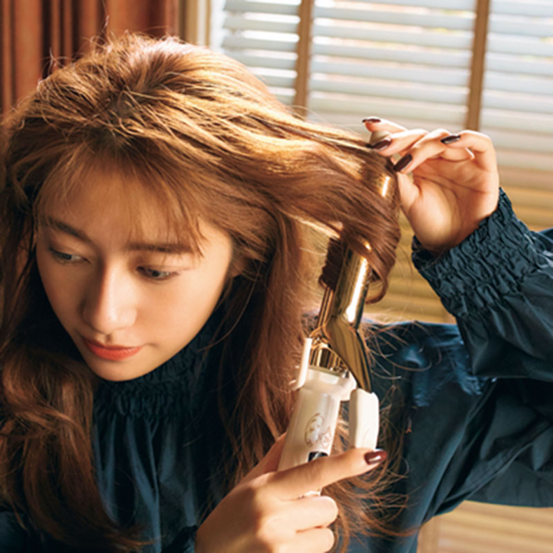 ①まずはバームを髪全体につけ、26㎜のコテで髪全体をMIX巻きしていきます。