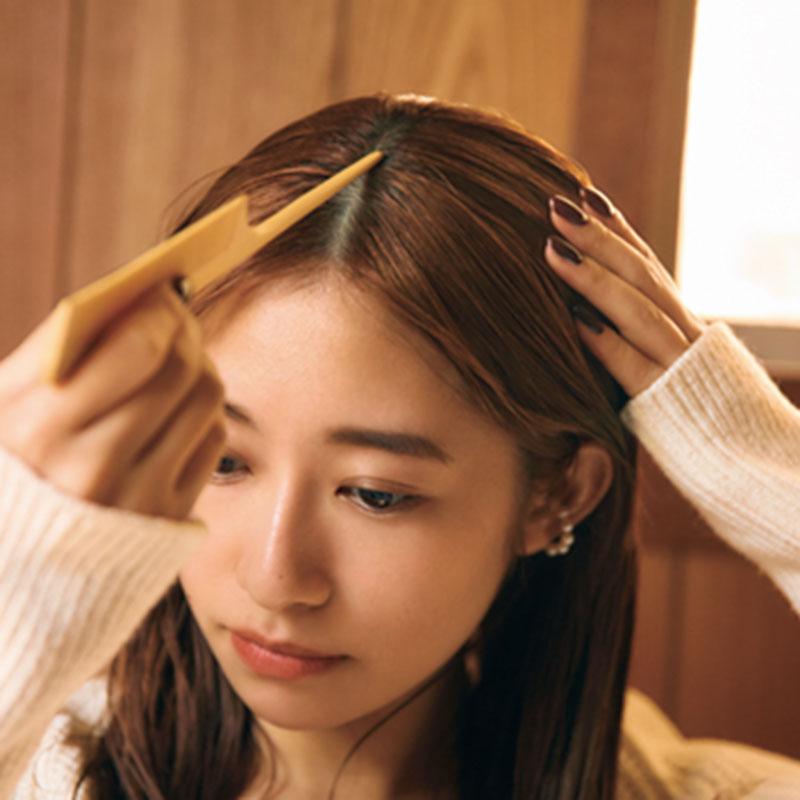③髪をセンターで分けます。コームの柄の先端を使って行うとキレイにキマります。