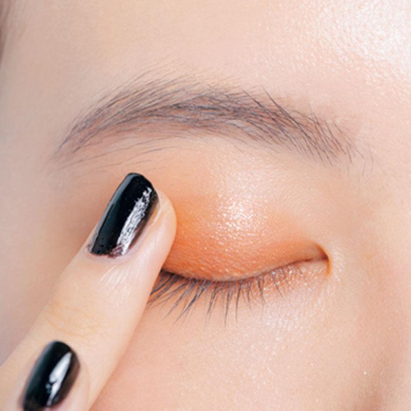 5. Dの艶ベージュを指の腹に取り、上まぶたの目頭半分にしっかり重ねます。